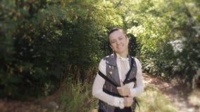 Счастливая девушка с малым рюкзаком на ее плечах, гуляя через древесину утра осени акции видеоматериалы