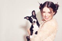 Счастливая девушка с щенком Женщина имеет потеху с ее собакой Владелец собаки имея потеху с любимцем Приятельство между человеком стоковая фотография