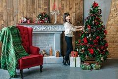 Счастливая девушка украшает рождественскую елку дома Концепция веселого Chr Стоковое Изображение