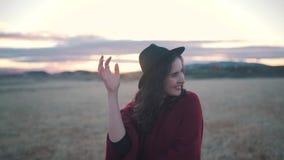 Счастливая девушка усмехается в поле на заходе солнца акции видеоматериалы