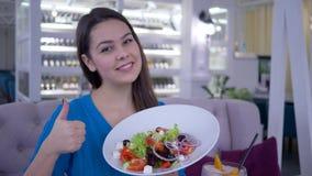 Счастливая диета, здоровая усмехаясь девушка ест полезную красивую еду от овощей для потери веса в ресторане сток-видео