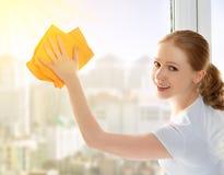 Счастливая домохозяйка девушки моет окно Стоковые Изображения