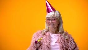 Счастливая достигшая возраста женщина в розовом пальто и круглых стеклах празднуя годовщину дня рождения стоковое изображение rf