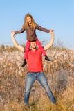 Счастливая дочь девушки отца и ребенка сидя на его голове стоковая фотография rf