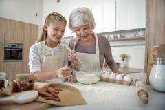 Счастливая еда бабушки и девушки смешивая с яичком в шаре Стоковое Фото