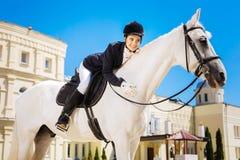 Счастливая женская склонность всадника на ее лошади белых гонок стоковые изображения rf