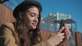 Счастливая женщина брюнета читая sms и осматривая изображения в смартф акции видеоматериалы