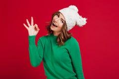 Счастливая женщина брюнет в свитере и смешной шляпе показывая о'кеы стоковые фото