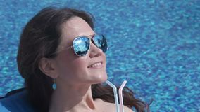 Счастливая женщина выпивая холодный коктеиль на poolside, улыбке на стороне видеоматериал