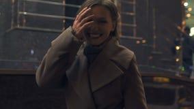 Счастливая женщина в ее 30s усмехаясь на улице, наслаждаясь городской жизнью ночи, стиль видеоматериал