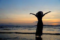 Счастливая женщина в заходе солнца моря на пляже в Таиланде стоковая фотография