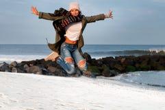 Счастливая женщина в куртках и теплой крышке скача на пляж в осени Стоковое фото RF