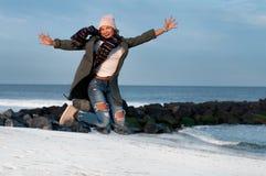 Счастливая женщина в куртках и теплой крышке скача на пляж в осени Стоковая Фотография