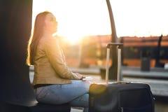 Счастливая женщина в поезде захода солнца ждать стоковые изображения rf