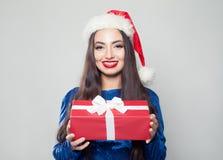 Счастливая женщина в расчалках и подарок рождества на белизне стоковые фото