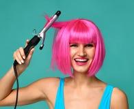 Счастливая женщина в розовом парике с железной керамической палочкой curler волос профессиональной завивая на голубой предпосылке Стоковое фото RF