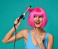 Счастливая женщина в розовом парике с железной керамической палочкой curler волос профессиональной завивая на голубой предпосылке Стоковые Фотографии RF