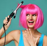 Счастливая женщина в розовом парике с железной керамической палочкой curler волос профессиональной завивая на голубой предпосылке Стоковые Изображения