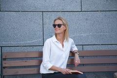 Счастливая женщина в солнечных очках сидя с книгой стоковая фотография rf