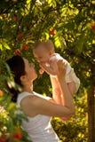 Счастливая женщина держа в руке младенца в саде семья счастливая Стоковая Фотография RF