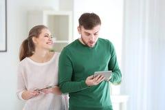 Счастливая женщина держа деньги и confused человека Стоковые Изображения