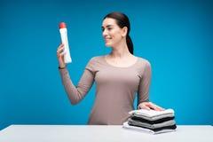 Счастливая женщина держа детержентной на таблице стоковое фото