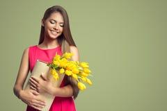 счастливая женщина держа корзину с желтыми тюльпанами стоковое фото rf