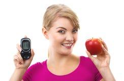 Счастливая женщина держа метр глюкозы и свежее яблоко, измеряя и проверяя концепцию сахара ровную стоковая фотография rf