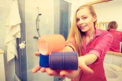 Счастливая женщина держа ролики волос в ванной комнате Стоковые Изображения