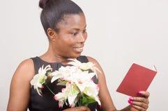 Счастливая женщина держа цветки и карточку стоковые изображения