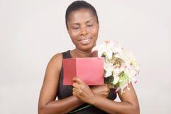 Счастливая женщина держа цветки и карточку стоковая фотография