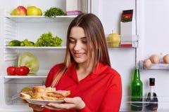 Счастливая женщина держит плиту с готовыми sandwhiches, носит красную блузку, идя иметь закуску, стойки перед раскрытым холодильн Стоковое Изображение