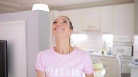 Счастливая женщина жонглирует с яблоками на кухне дома видеоматериал