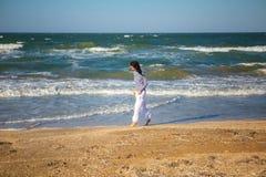 Счастливая женщина идя на пляж на заходе солнца стоковое фото