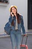 Счастливая женщина идя с багажом и говоря на мобильном телефоне снаружи Стоковая Фотография