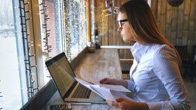 Счастливая женщина используя компьтер-книжку на кафе Молодая красивая девушка сидя в кофейне и работая на компьютере сток-видео