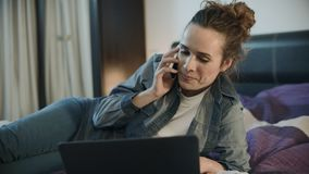 Счастливая женщина используя телефон и ноутбук для работы онлайн дома акции видеоматериалы