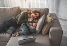 Счастливая женщина и ребенок обнимая на софе пока играющ Стоковые Фото