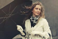 Счастливая женщина моды в белом пальто канавы идя в улицу города стоковые фотографии rf