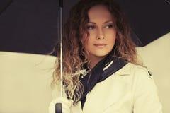 Счастливая женщина моды в белом пальто канавы идя в улицу города стоковое фото rf