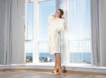 Счастливая женщина наслаждаясь взглядом моря в гостинице/комнате стоковые изображения