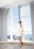 Счастливая женщина наслаждаясь взглядом моря в гостинице/комнате стоковая фотография