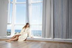 Счастливая женщина наслаждаясь взглядом моря в гостинице/комнате стоковые изображения rf