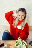 Счастливая женщина наслаждаясь некоторым кофе в кафе стоковые фото