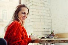 Счастливая женщина наслаждаясь некоторым кофе в кафе стоковое фото