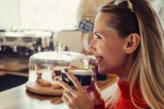 Счастливая женщина наслаждаясь некоторым кофе в кафе стоковое изображение rf