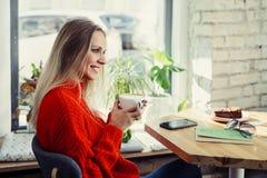 Счастливая женщина наслаждаясь некоторым кофе в ресторане стоковые фото