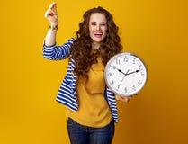 Счастливая женщина на желтой предпосылке с пальцами часов щелкая стоковые фотографии rf