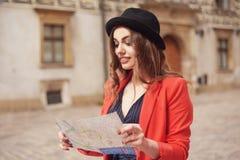 Счастливая женщина на каникулах с картой, путешественник идет город день солнечный задний взгляд Молодая туристская женщина в шля Стоковая Фотография RF