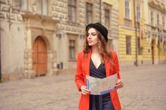 Счастливая женщина на каникулах с картой, путешественник идет город день солнечный задний взгляд Молодая туристская женщина в шля Стоковые Изображения RF
